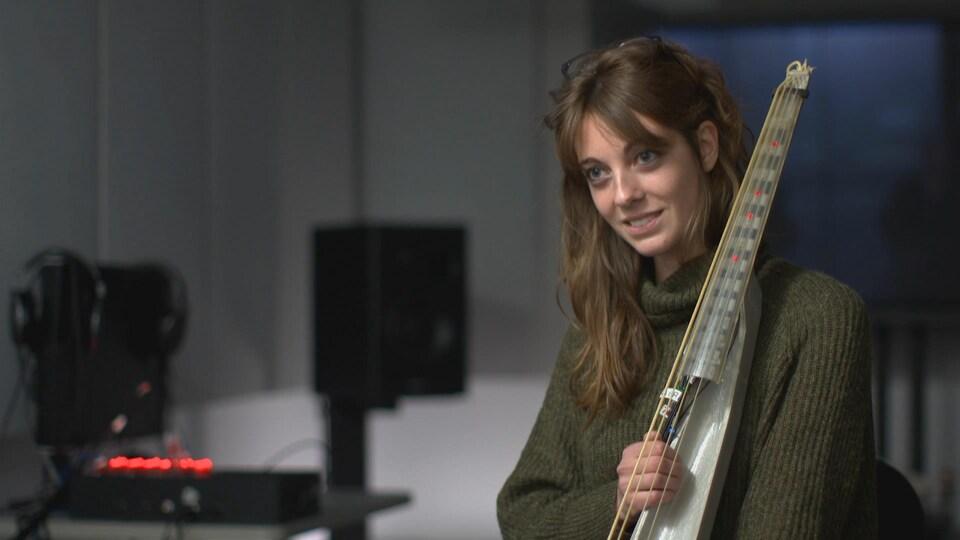 Indiana Wollman, chercheuse postdoctorale en neurosciences à l'Université McGill, et l'instrument à cordes utilisé pour l'expérience sur l'activité cérébrale et le talent musical.