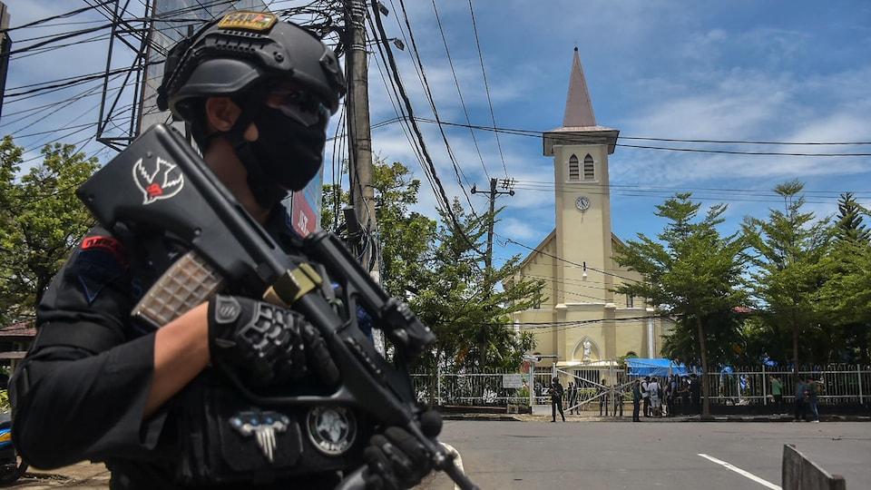 Un policier indonésien devant une église.