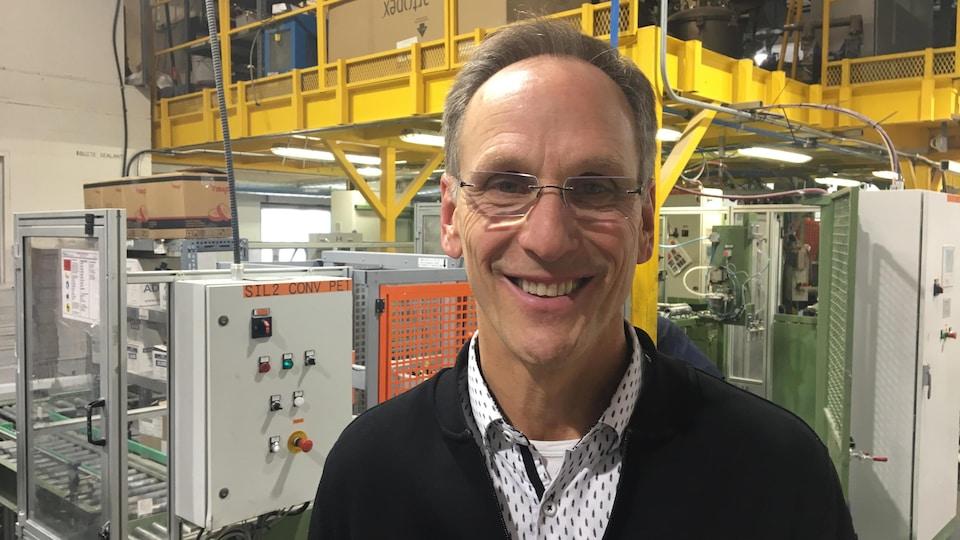 Il sourit dans une salle de son usine.