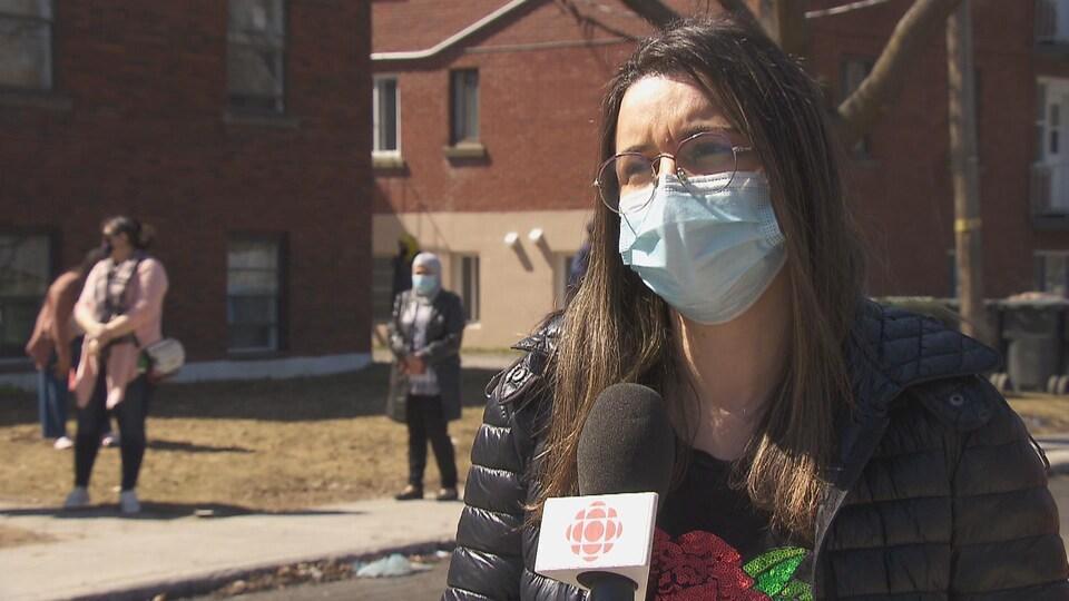 Elle est dehors, porte un masque et parle dans un micro.