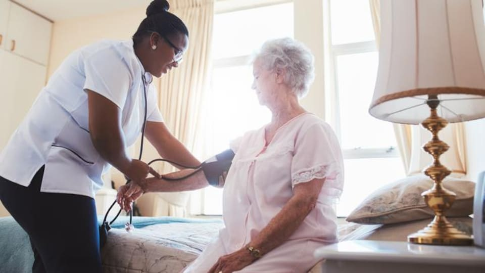 Une infirmière prend la pression d'une patiente.
