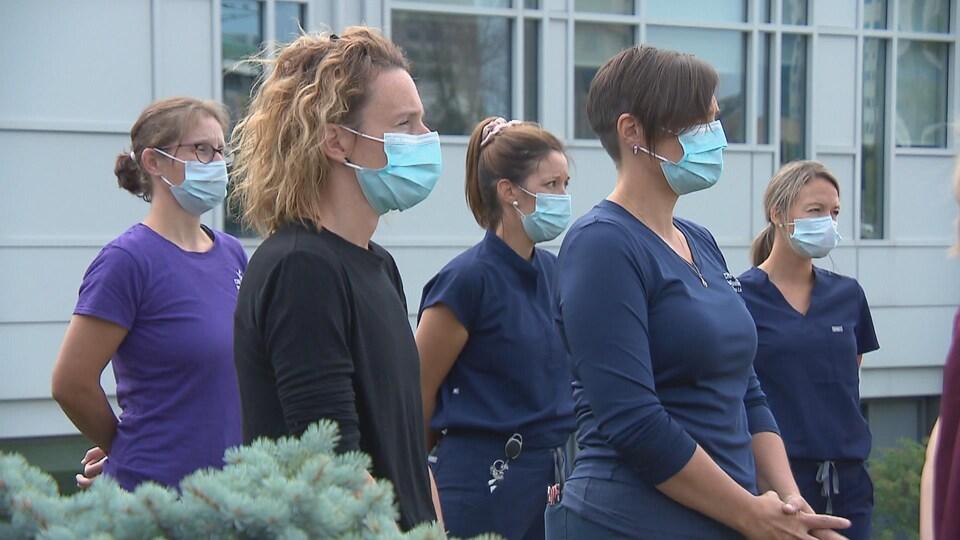 Des femmes et un homme en tenue d'hôpital se tiennent debout en extérieur.