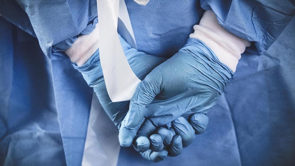 Une infirmière qui porte des gants de caoutchouc joint se mains derrière son dos.
