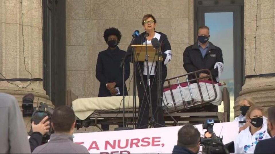 Des personnes avec un lit placé derrière Darlene Jackson qui parle dans des micros.