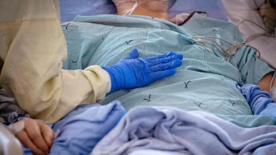 Une infirmière s'occupe d'un patient dans une unité de soins intensifs.