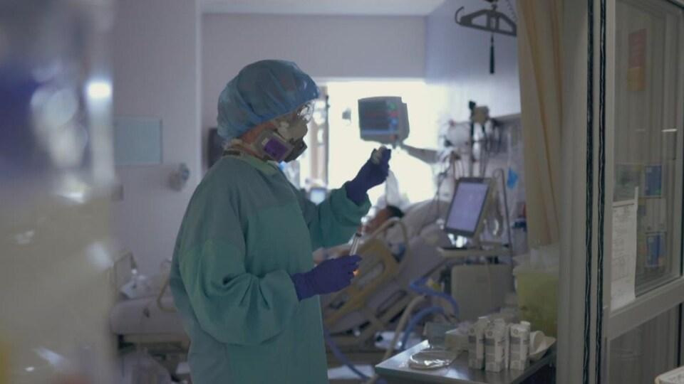 Une infirmière porte un masque, des gants et un équipement protecteur.