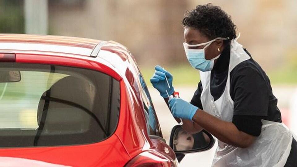Une infirmière effectue un prélèvement sur une personne à bord d'une voiture.