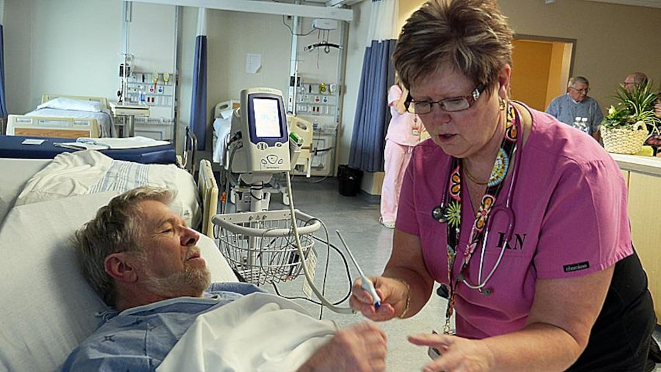 Une infirmière soigne un patient.