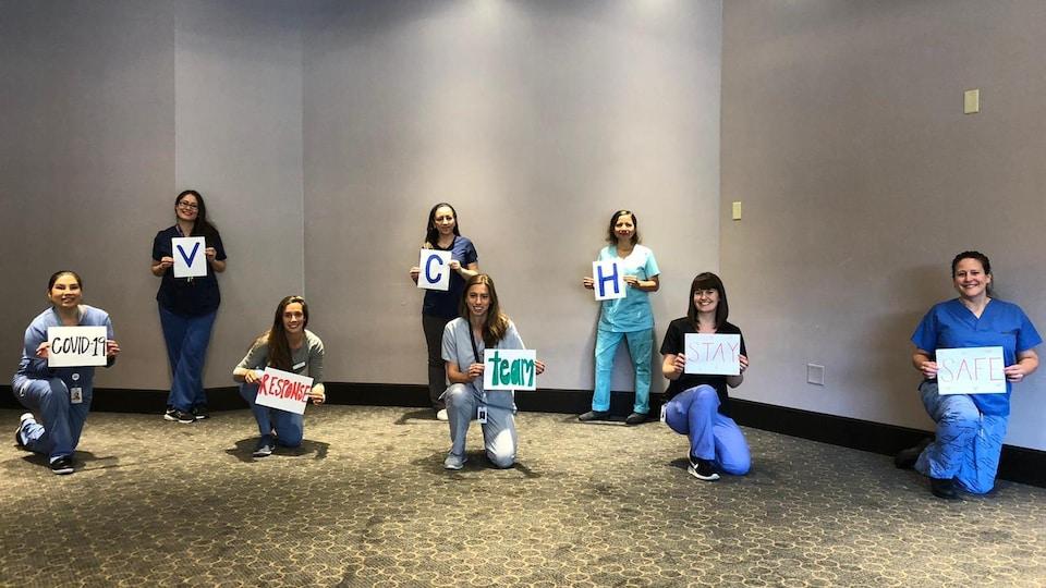 8 infirmières portent des feuilles où il est écrit « VCH COVID-19 response team stay safe ».