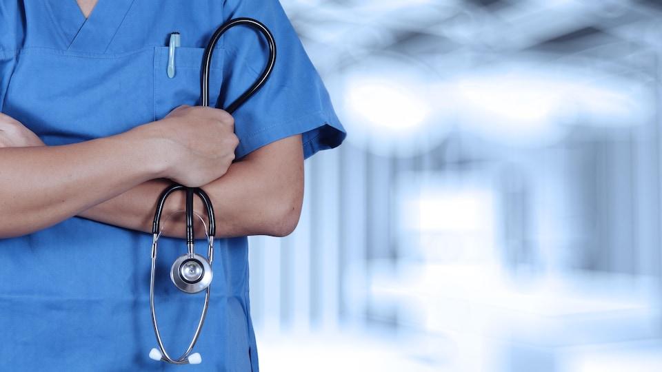 Un travailleur de la santé se tient debout les bras croisés avec un stéthoscope en main.