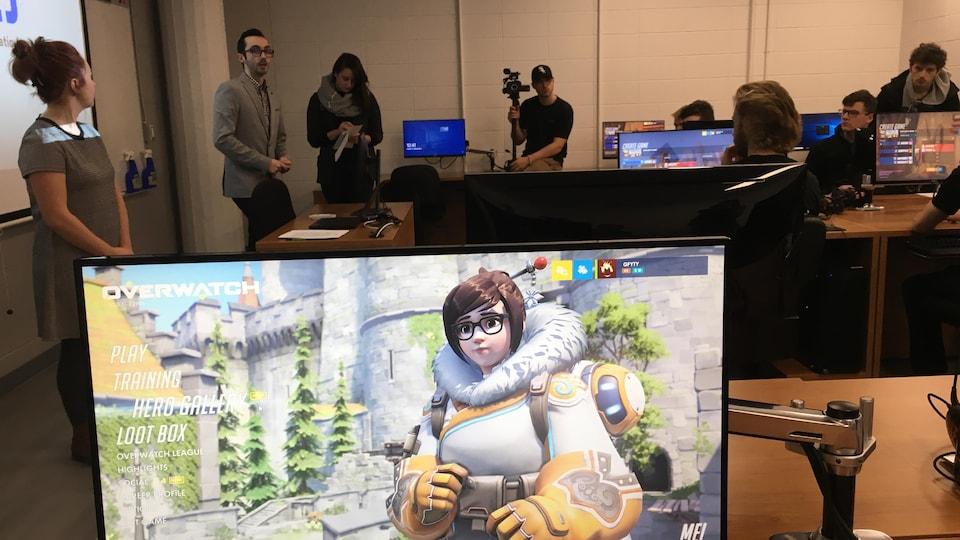Un laboratoire d'informatique. On voit un écran sur lequel un jeu vidéo apparaît et des personnes assises derrière leurs ordinateurs derrière.