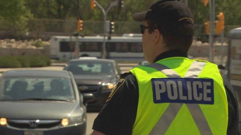 Un policier de Winnipeg debout qui veille à la circulation.