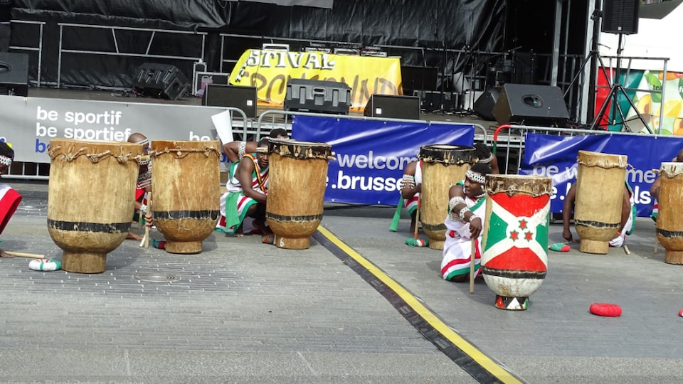 7 tambourinaires du groupe Ikiyago Legacy accroupis chacun devant un tambour.
