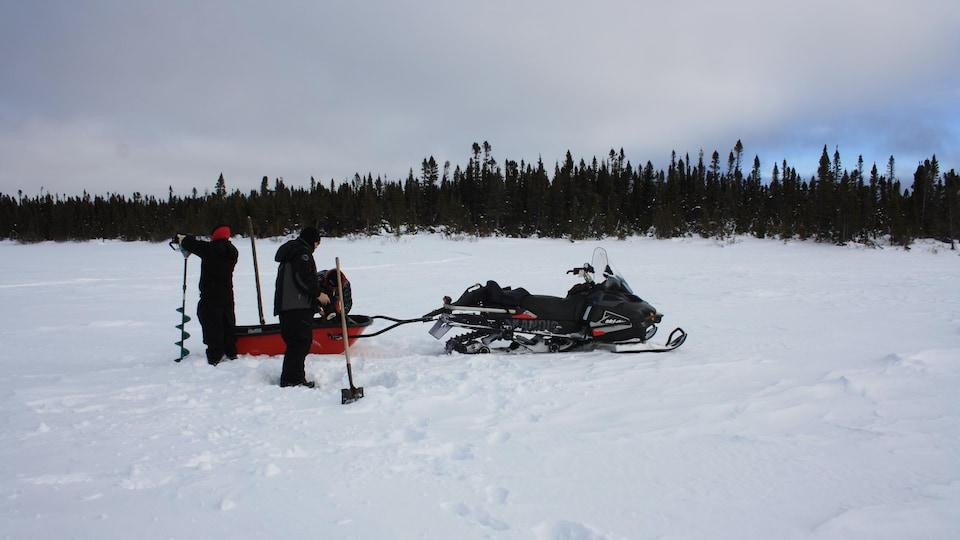 Des hommes en habit d'hiver prêt d'une motoneige sur une étendue enneigée.