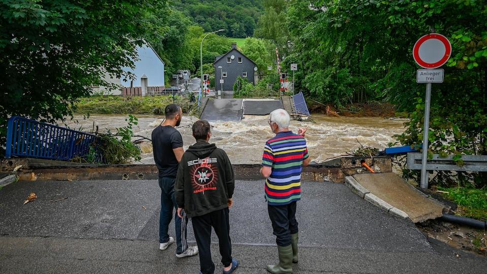 Trois personnes regardent un pont effondré sur une rivière.
