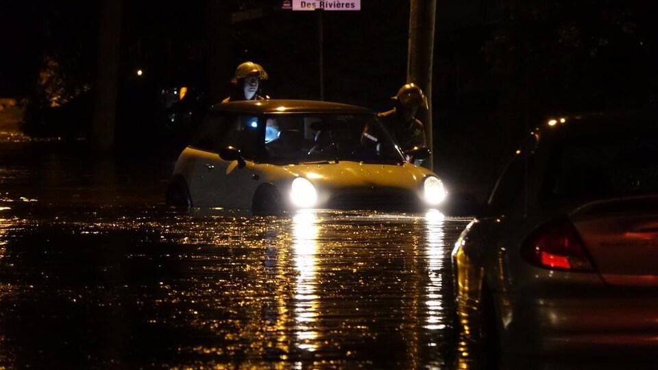 De l'eau à la hauteur des feux de route d'une voiture