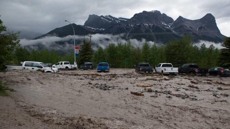 De l'eau boueuse charriant des débris a envahi un concessionnaire automobile à Canmore.