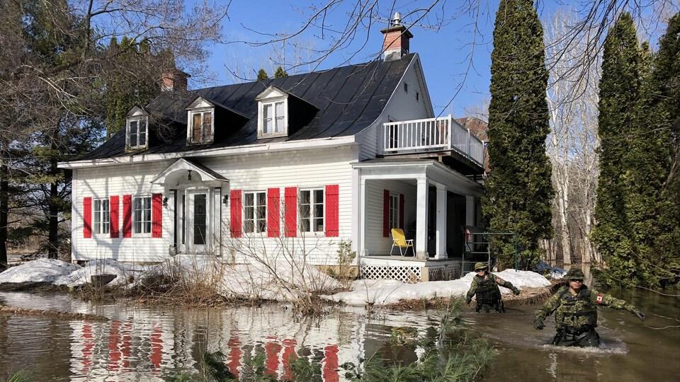 Des militaires ont de l'eau jusqu'à la taille sur le terrain d'une résidence de Champlain.