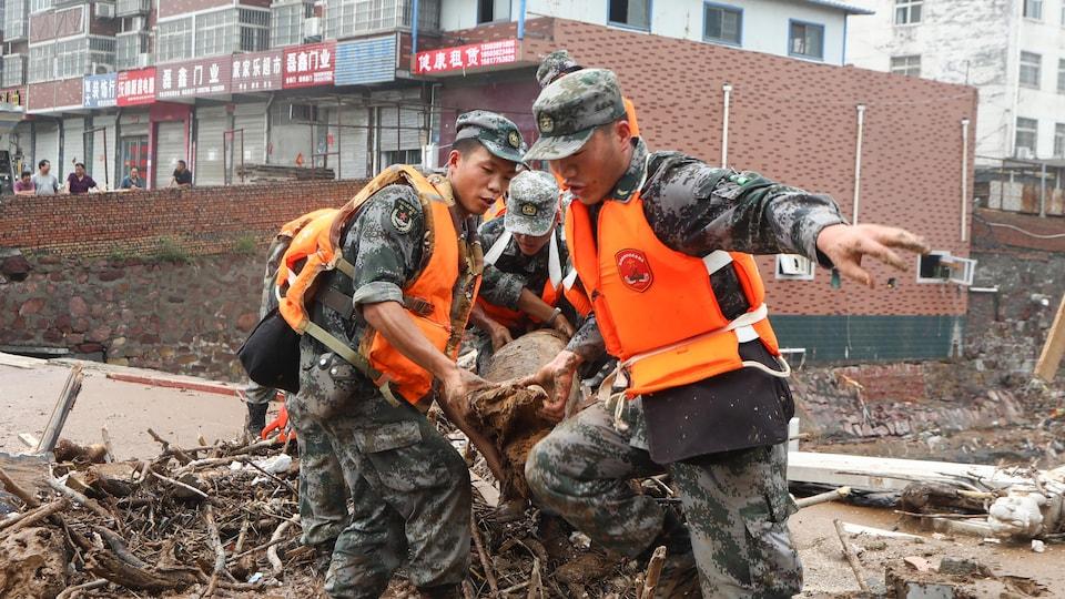 Des soldats transportent des débris.