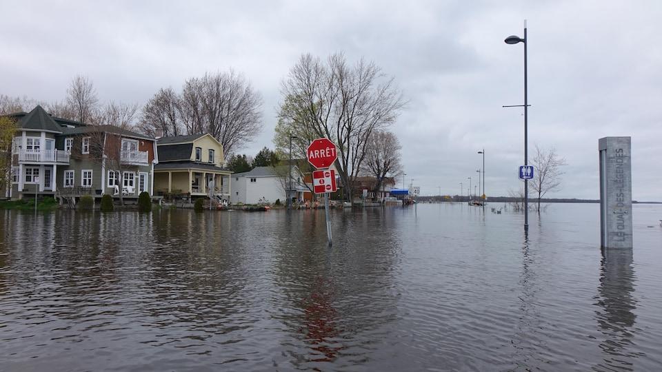 Un panneau d'arrêt sort de l'eau sur une rue inondée de Gatineau.
