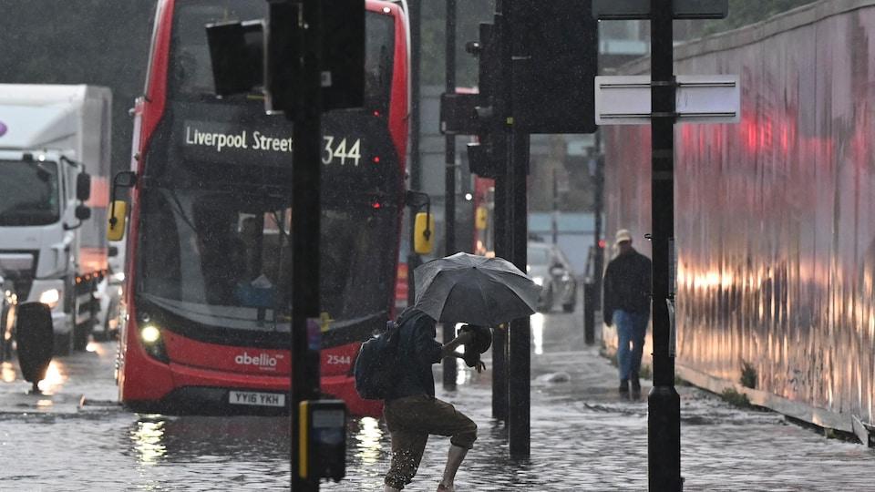 Des piétons et des véhicules dans une rue inondée.