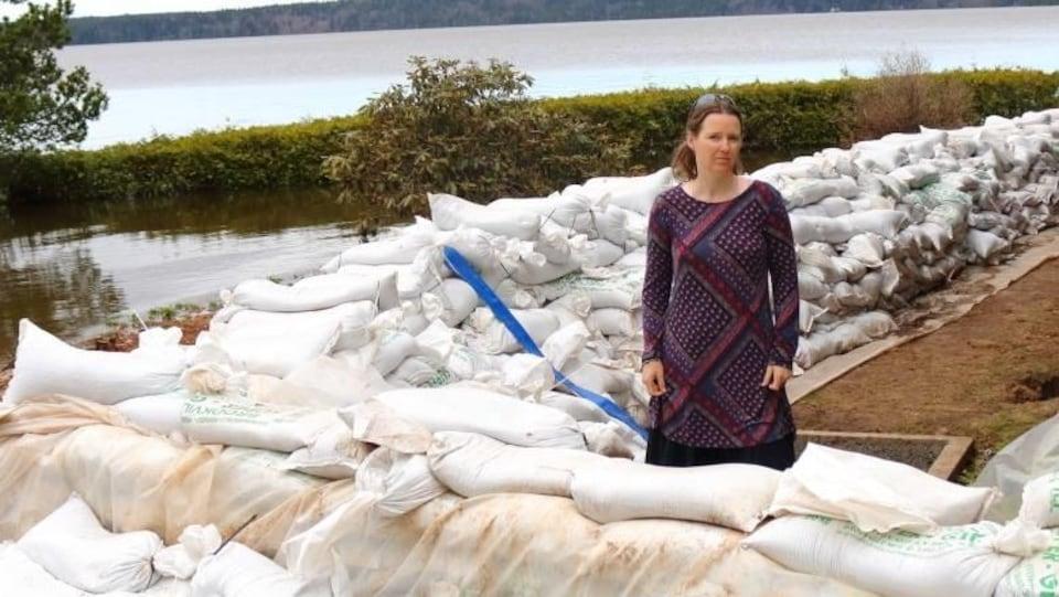 Un dame debout à côté de murets en sacs de sable.