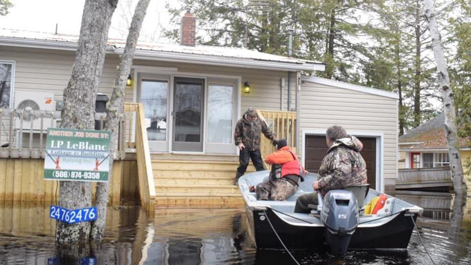 Des hommes dans une chaloupe amarrent leur embarcation au balcon d'une maison.