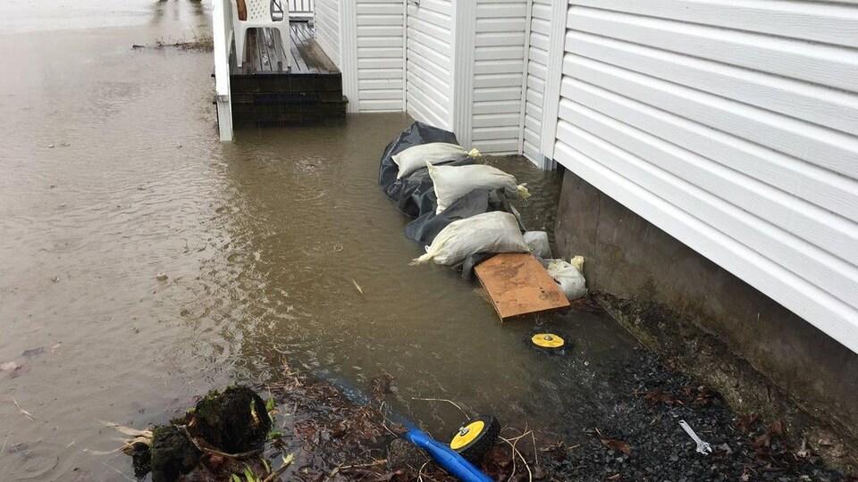 Des sacs de sable et une pompe autour d'une maison inondée.