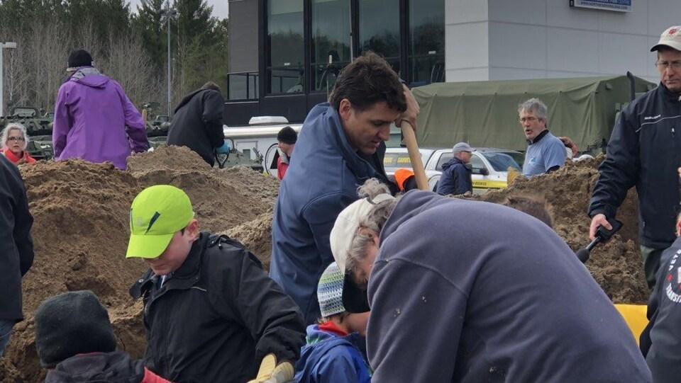 Plusieurs personnes avec des pelles remplissent des sacs de sable.