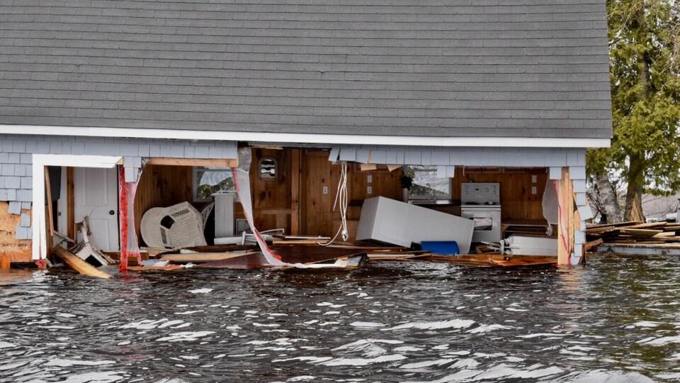 Vue de l'intérieur d'une habitation inondée dont un mur est presque complètement arraché.