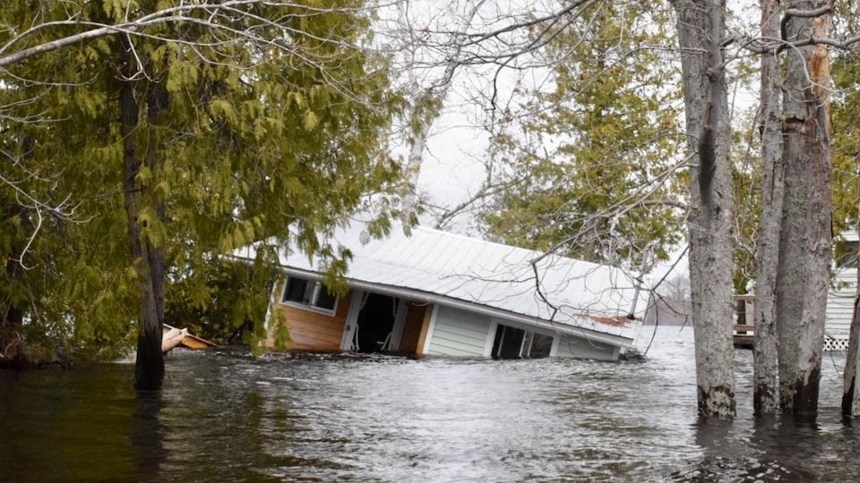 Habitation emportée par les inondations et submergée sur le côté à Princess Park, dans la région de Grand Lake au Nouveau-Brunswick, le 28 avril 2019.