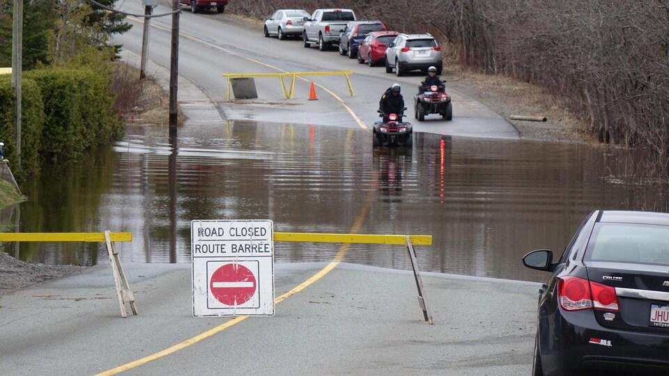 Deux personnes en VTT traversent une section de route inondée interdite à la circulation.