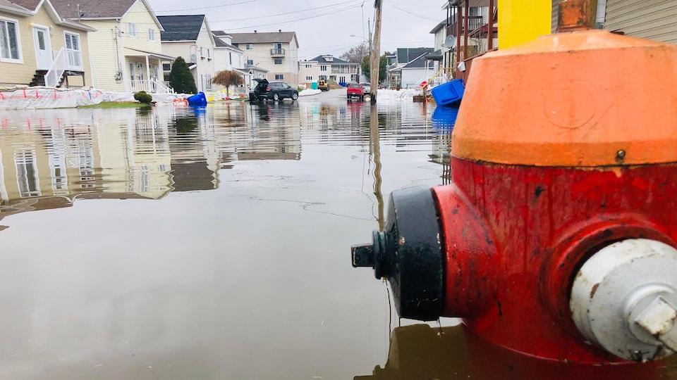 Une borne-fontaine à proximité de résidence est immergée aux deux tiers.