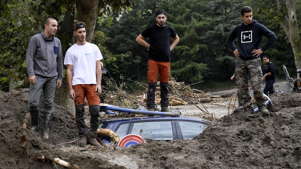 Des hommes regardent impuissants un véhicule partiellement submergé dans une rue de Breil-sur-Roya, dans le sud-est de la France.