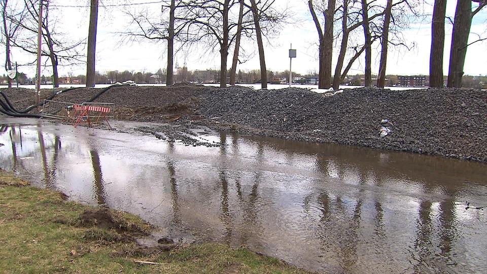 Une digue faite de petites roches sépare la rivière des Prairies de L'Île-Bizard.