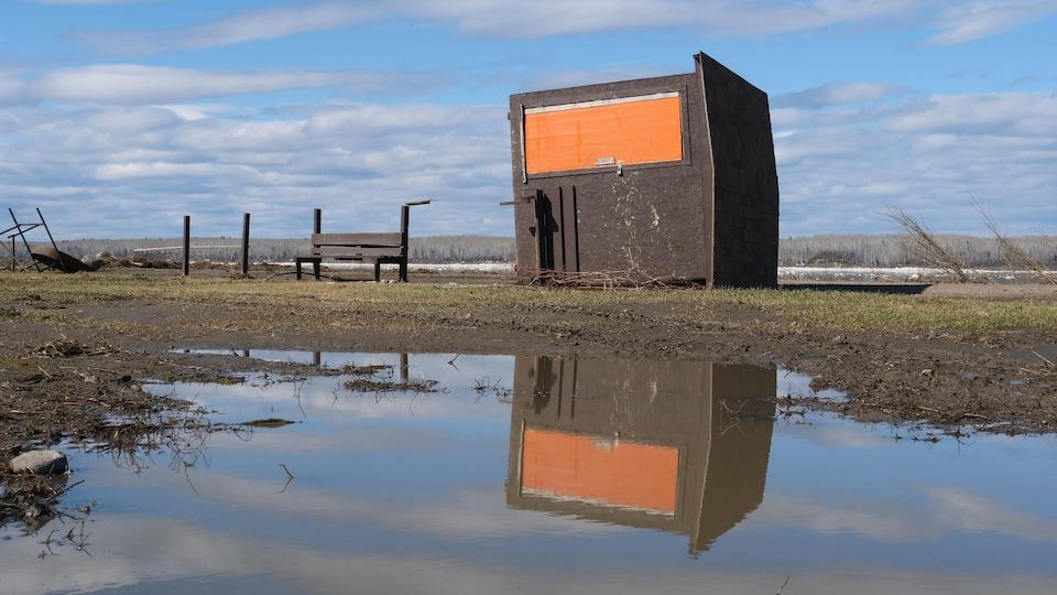 Une cabane à la porte orange sur le côté et son reflet dans une flaque d'eau.