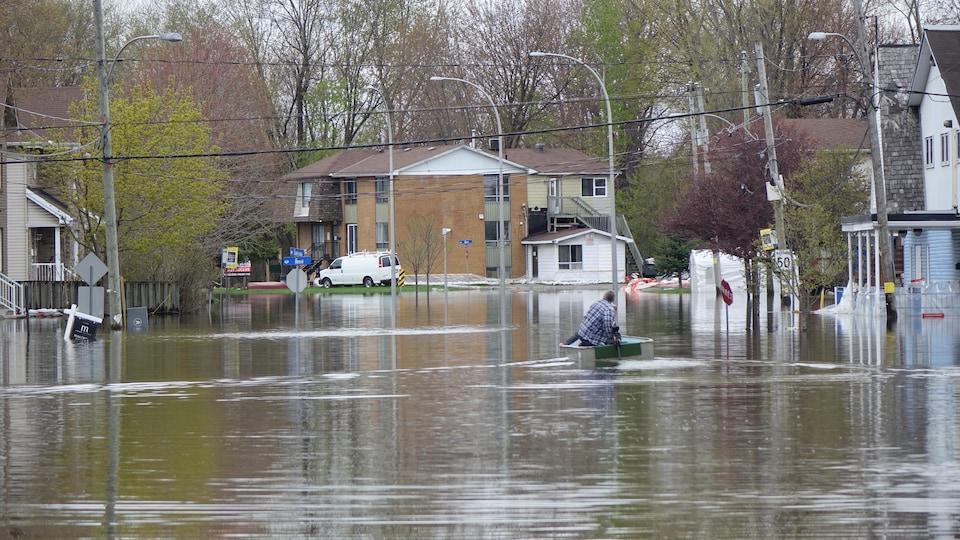 Deux personnes en chaloupe sur une rue inondée.