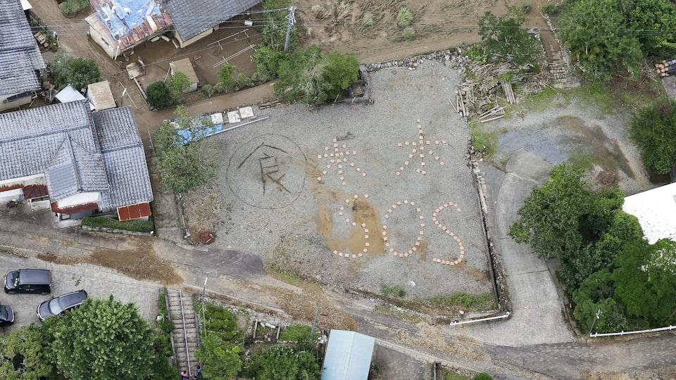 Les mots «Rice, Water, SOS» inscrits au sol sur le terrain de l'école avec des pierres ou des briques.
