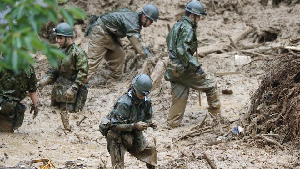 Des hommes ont les pieds dans la boue et leur uniforme est mouillé alors qu'ils cherchent des survivants.