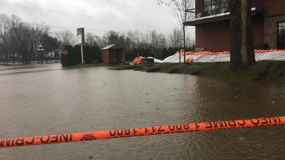 Une rue inondée, un ruban orange désigne l'interdiction de passer.