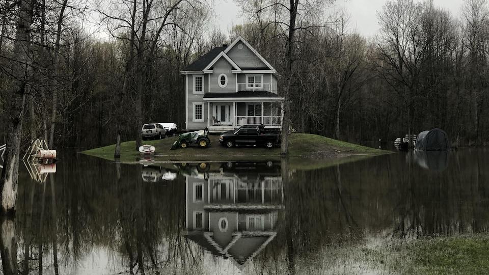 Une maison de deux étages sur une butte de terre entourée par l'eau