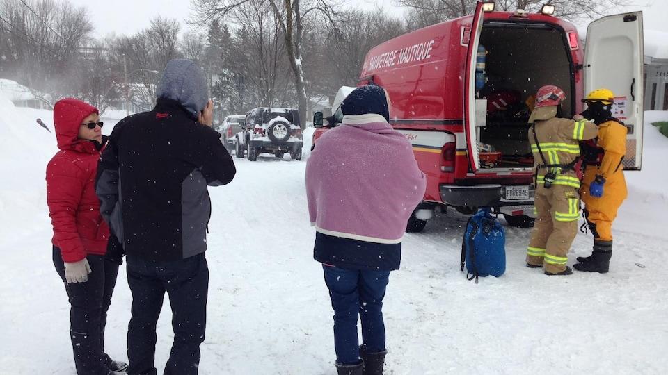 Des évacués du quartier Duberger-Les Saules à Québec près d'un véhicule d'urgence