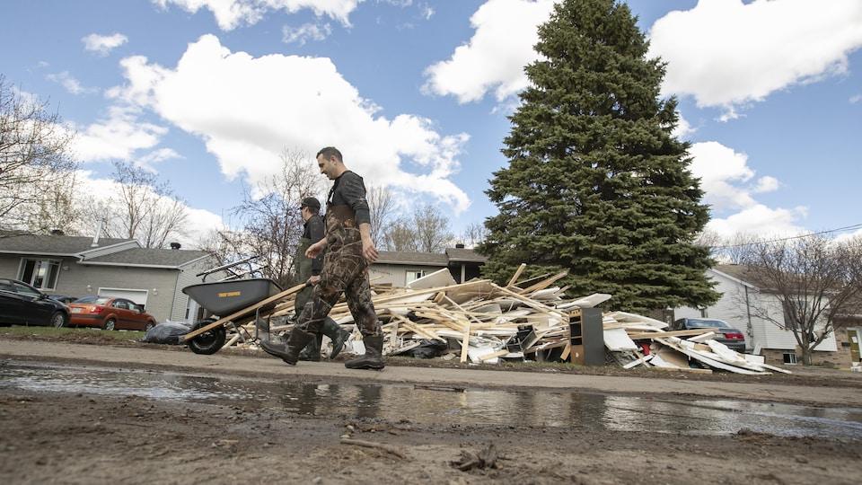 Deux hommes portant des vêtements de travail marchent devant un tas de débris, posé sur le terrain avant d'une maison.