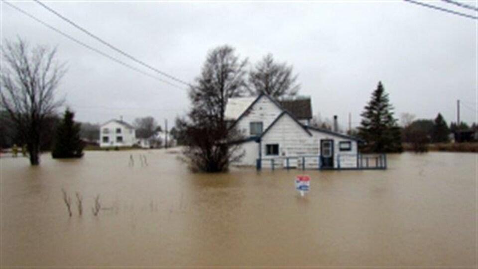De l'eau brune entoure deux maisons blanches. L'eau atteint la porte d'une des maisons.
