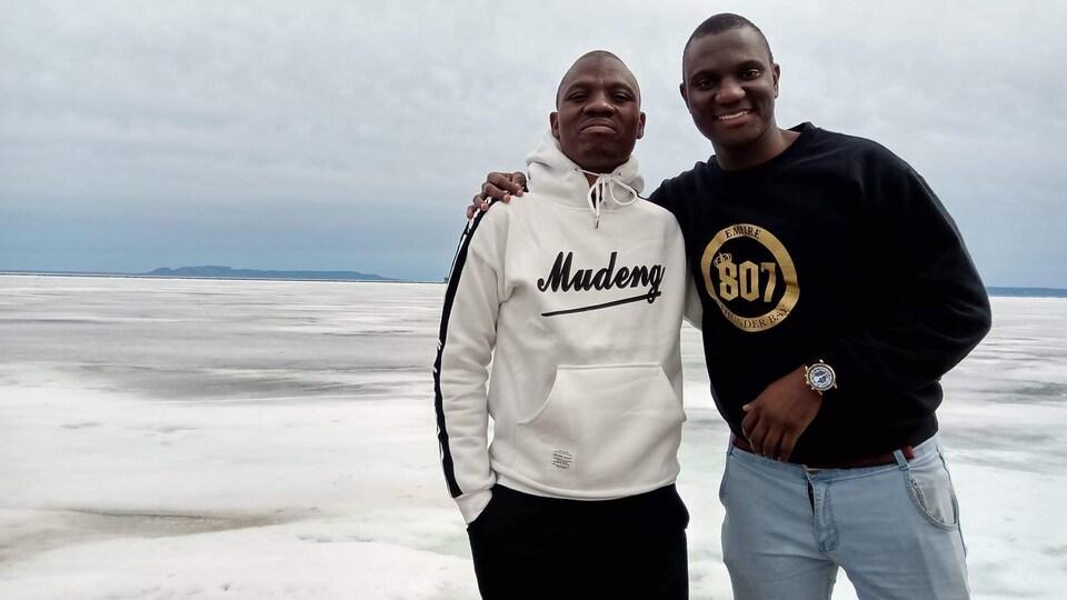 Deux hommes noirs debout devant un lac partiellement gelé