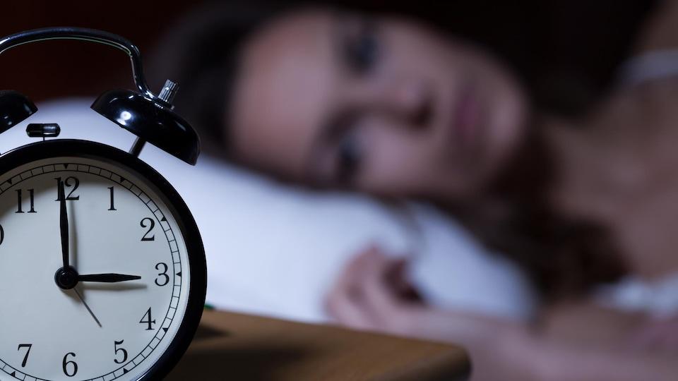 Une personne, dans son lit, fixe son réveil-matin.