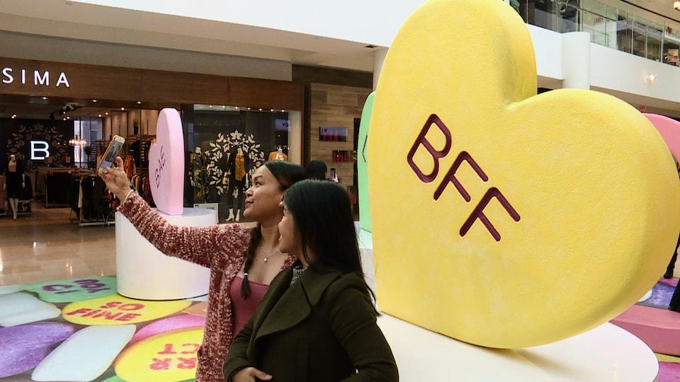 Deux femmes prennent un égoportrait devant un coeur géant avec l'inscription BFF.