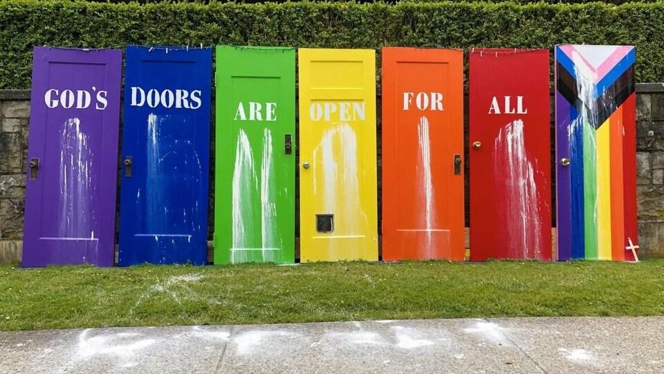 Des mots écrits en anglais sur sept portes colorées forment la phrase « Les portes de Dieu sont ouvertes à tous ».