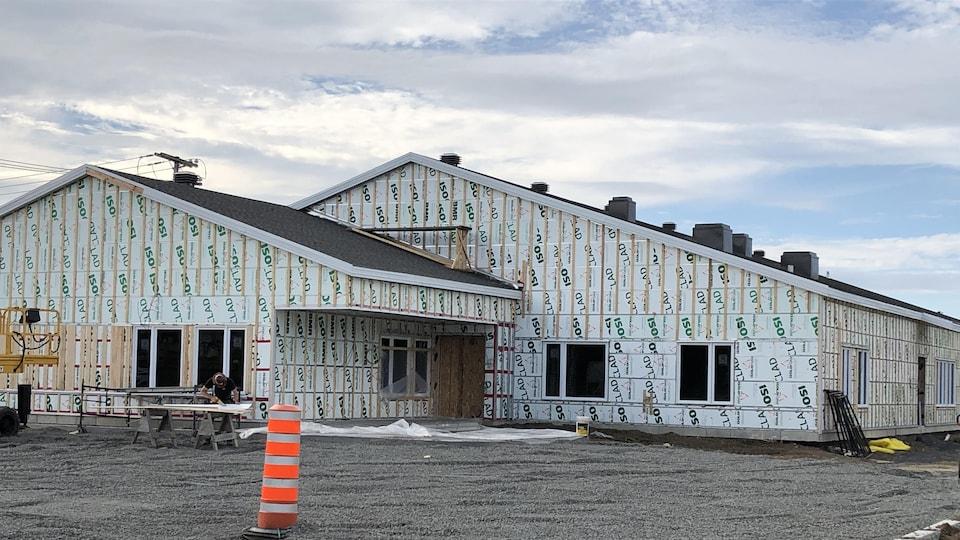 Un homme travaille devant l'édifice en construction.