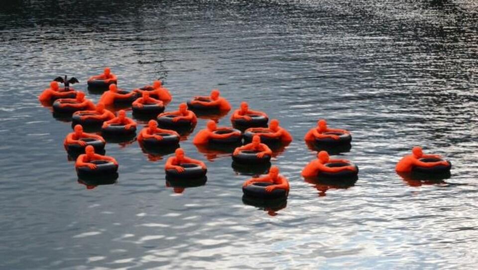 Plusieurs effigies représentant des humains orange agrippant des bouées noires.